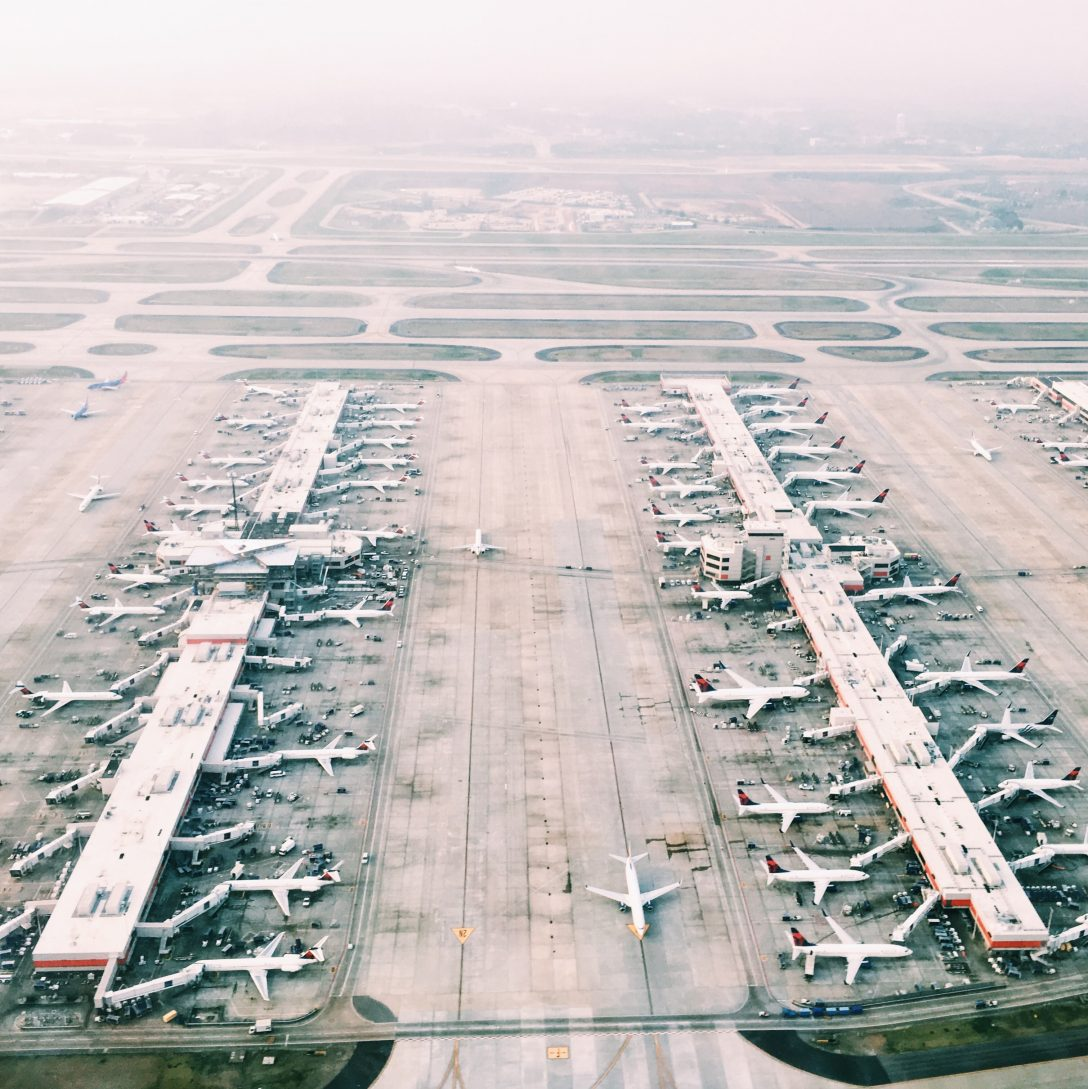 Aerial view of planes docked at two airport terminals.