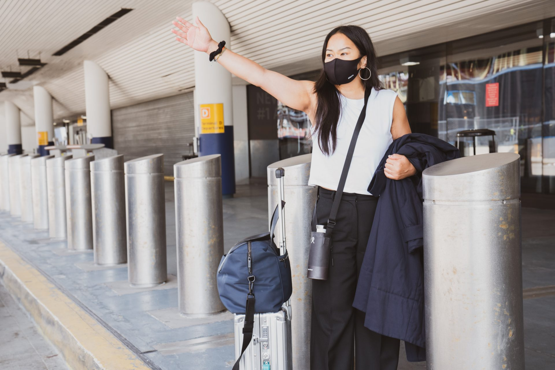 Woman waving at someone outside an airport.