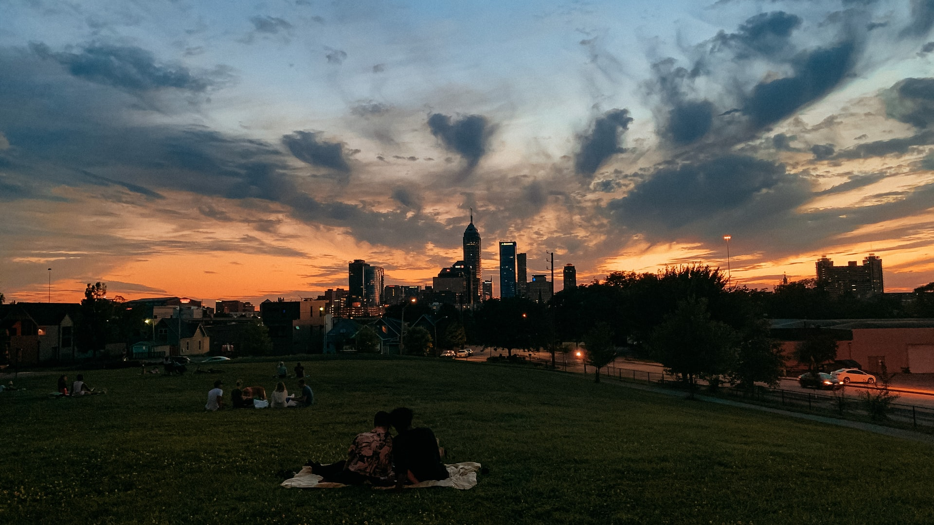 People sitting in a park looking at a skyline of Indianapolis at sunset.