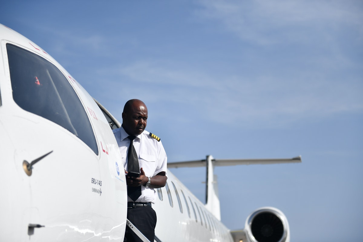 Pilot stands at the door of an airplane.