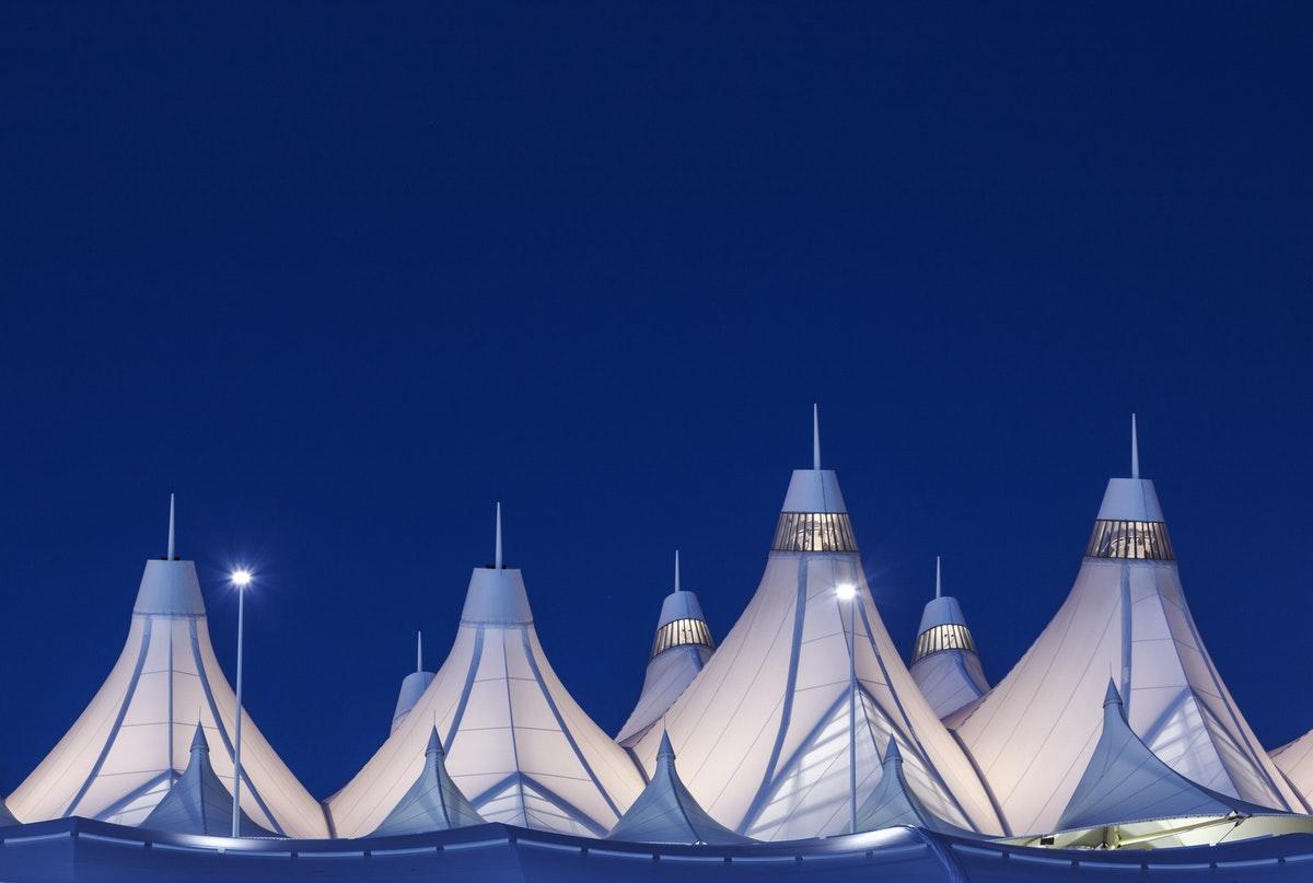 Peaked roof of Denver International Airport at nighttime.