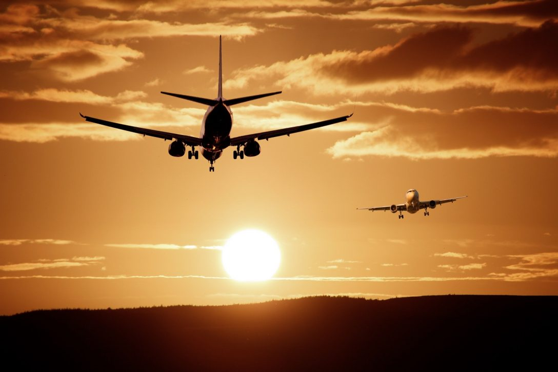 Two airplanes taking off and landing at sunset.